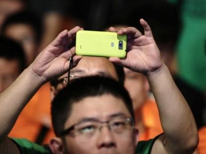 Un uomo fa una foto con uno smartphone Xiaomi